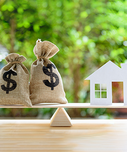 Image of a House and Money Bags on a Scale for Home Equity Loans
